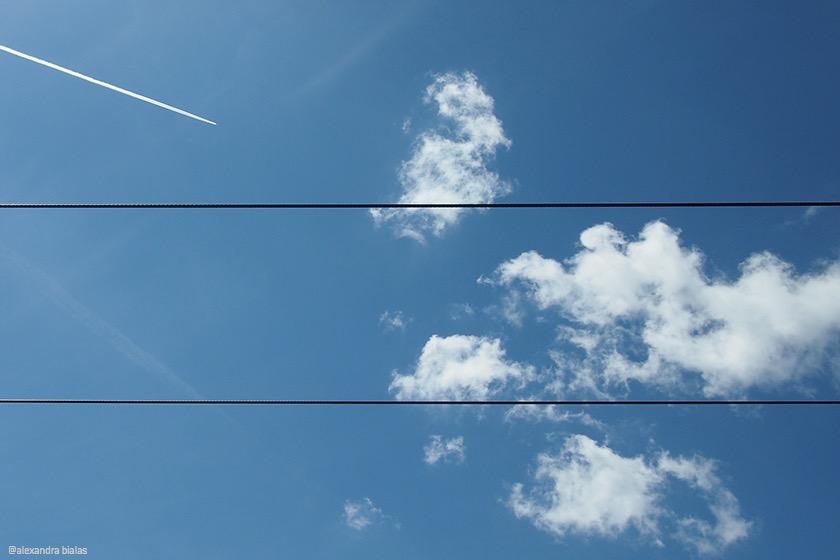 Blick auf blauen Himmel mit weißen Wolken, Kondensstreifen und zwei Stromleitungen, die horizontal verlaufen.
